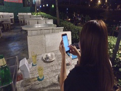 Asian woman plays on phone at thai outdoor restaurant Stock Footage