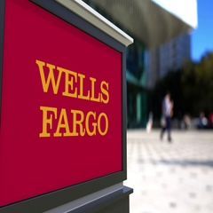 Street signage board with Wells Fargo logo. Blurred office center and walking Stock Footage