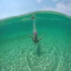 UNDERWATER: Beautiful girl with long brown hair swimming underwater in ocean Stock Footage