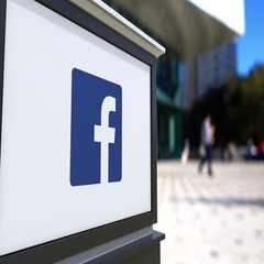 Street signage board with Facebook logo. Blurred office center and walking Stock Footage