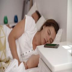 Woman in bed woken by smartphone, wakes sleeping partner Stock Footage