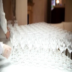 Waiter puts a lot of empty glasses on white table cloth Stock Footage