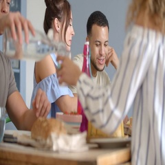 Young adult friends drinking and eating at a friends dining table Stock Footage