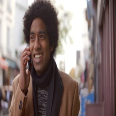 Young Man Using Phone As He Walks Along Busy City Street Stock Footage
