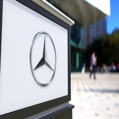 Street signage board with Mercedes-Benz logo. Blurred office center and walking Stock Footage