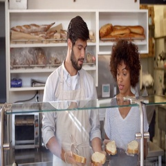 Manager training a woman behind the counter at sandwich bar Stock Footage