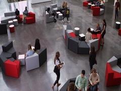 Elevated pan shot of students in busy university lobby area, shot on R3D Stock Footage