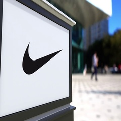 Street signage board with Nike logo. Blurred office center and walking people Stock Footage