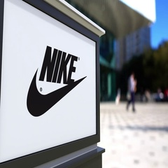 Street signage board with Nike inscription and logo. Blurred office center and Stock Footage