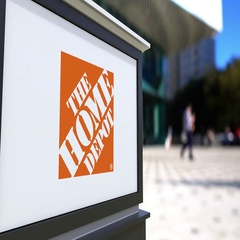 Street signage board with The Home Depot logo. Blurred office center and walking Stock Footage