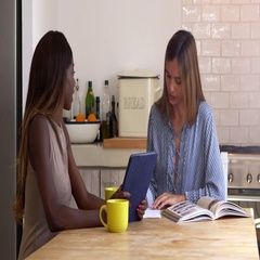 Two female friends researching recipes at the kitchen table, shot on R3D Stock Footage