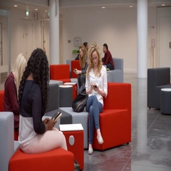 Students relax and socialise in the lobby of a university Stock Footage