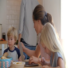 Kids working at kitchen table with mum while dad cooks Stock Footage