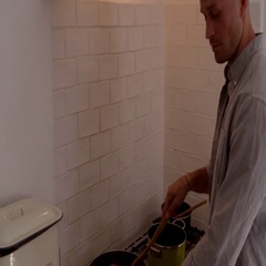 Dad cooking and mum with kids at the kitchen table, shot on R3D Arkistovideo