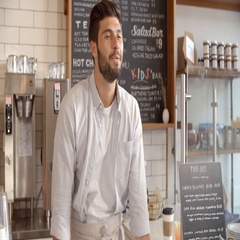 Barista taking card payment from a customer at a coffee shop Stock Footage