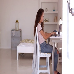Girl using a laptop in bedroom answers her phone, full length, shot on R3D Stock Footage