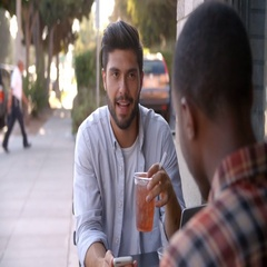Two adult male friends talking over cold drinks outside cafe Stock Footage