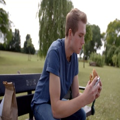 Young white man sitting on a park bench enjoying a burger Stock Footage