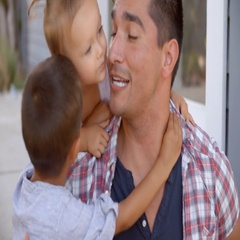 Father Hugging Children Sitting On Steps Outside Home Stock Footage