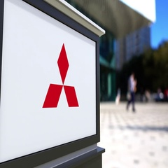 Street signage board with Mitsubishi logo. Blurred office center and walking Stock Footage