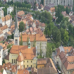 Sunlit ancient Saint James Parish Church in Slovenia, sunny green Ljubljana, pan Stock Footage