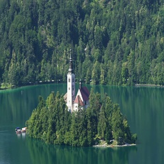Secluded island with church surrounded by Lake Bled and Alps, spirituality Stock Footage