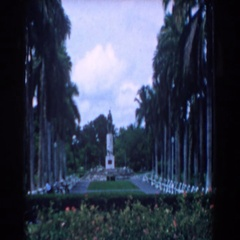 1958: a park with monument in background and man walking in the forefront Stock Footage