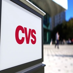 Street signage board with CVS Health logo. Blurred office center and walking Stock Footage