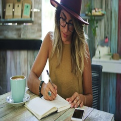 Woman writing in journal in cafe Stock Footage