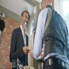 4K Friendly barber taking payment from satisfied customer in barber shop Stock Footage