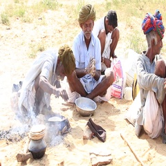 Indian men cook food on a fire attended the annual Pushkar Camel Mela. India Stock Footage