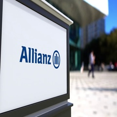Street signage board with Allianz logo. Blurred office center and walking people Stock Footage