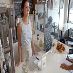 Customer at coffee shop pays smiling waitress with card Stock Footage