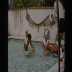 1961: dad teaching kid to swim at swimming party NORTH HOLLYWOOD, CALIFORNIA Stock Footage