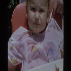 1964: child sitting in highchair with a bib being fed food with a spoon  Stock Footage