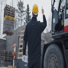 Construction Worker Signals to Crane Operator on Construction Site.  Stock Footage