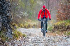 Biker with mountain bike downhill on dirt road Stock Photos