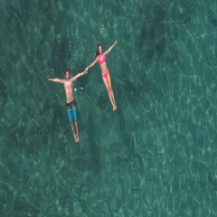 AERIAL: Smiling couple swimming in sea, floating on water surface holding hands Stock Footage