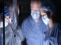 Surgical team works with saline drip in foreground 4K Stock Footage