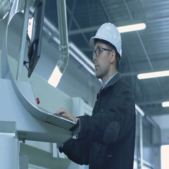 Engineer in Hard Hat Setting Up CNC Machine at the Factory.  Stock Footage