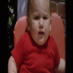 1964: unhappy baby sitting in high chair soothed when given milk bottle  Stock Footage