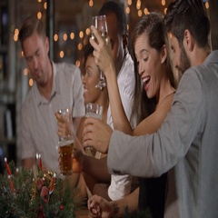 Friends celebrating together at a Christmas party in a bar Stock Footage