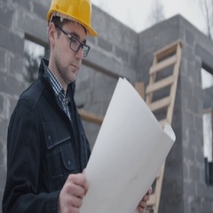 Young Construction Worker Looking at Large Blueprint.  Stock Footage