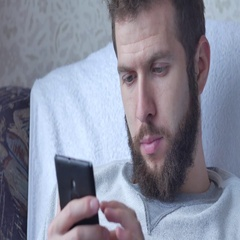 One white young brunette curly-bearded man uses the phone sitting in resle Stock Footage