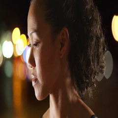 Mixed race woman athlete standing outdoors at night looking at camera Stock Footage