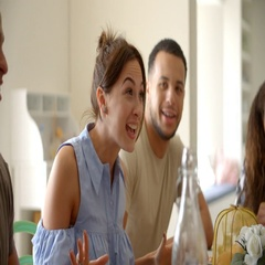 Young adult friends sitting at a table talking, close up Stock Footage