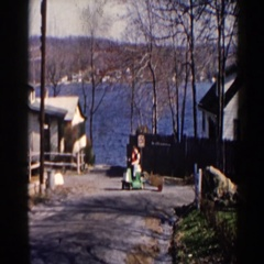1964: family playing with their son, riding around on a toy train. PEQUOT LAKES Stock Footage