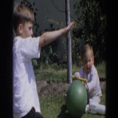 1964: kids play with toys in yard. NORTH HOLLYWOOD, CALIFORNIA Stock Footage