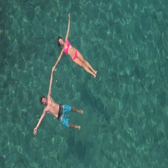 AERIAL: Loving couple on dreamy holidays swimming starfish float holding hands Stock Footage