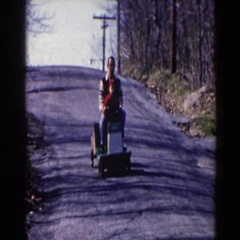 1964: father and son taking a ride on a toy train down their driveway Stock Footage